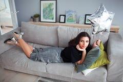 Den armeniska brunettflickan ligger på en soffa med en ballong i formen av en stjärna bekväm inre modern sofa 3d Arkivbilder