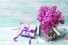 Den aromatiska lilan blommar i vas och boxas med gåvor på turquois Arkivbilder
