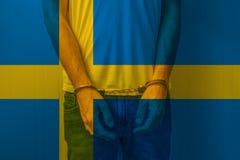 Den arresterade mannen med örfilade upp händer som bär skjortan med svensk, sjunker Arkivfoton
