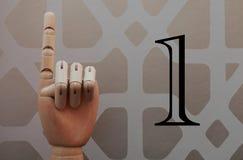 Den artikulerade trähanden med ett finger lyftte i allusion för att numrera en royaltyfri fotografi