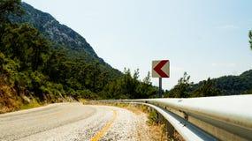 Den asfalterade vägbortgången i bergen Arkivfoto