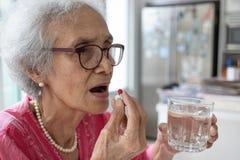 Den asiatiska äldre kvinnan är ta och äta mediciner och vitaminer arkivfoto
