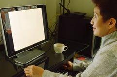 Den asiatiska äldre kvinnan tycker om att arbeta med persondatorn Royaltyfria Bilder