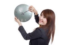 Den asiatiska affärskvinnaflyttningen en klockahand och vänder tillbaka Royaltyfri Foto