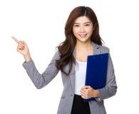 Den asiatiska affärskvinnahållen med skrivplattan och fingret pekar upp Arkivfoton