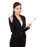 Den asiatiska affärskvinnahållen med skrivplattan och fingret pekar upp Royaltyfria Bilder