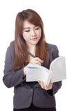 Den asiatiska affärskvinnan är tänka och skriva anmärkningen i en bok Arkivbilder