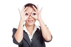 Den asiatiska affärskvinnan gör det roliga dubbla reko tecknet som exponeringsglas Arkivfoton