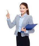 Den asiatiska affärskvinnan med skrivplattan och fingret pekar upp Royaltyfri Foto