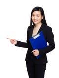 Den asiatiska affärskvinnan med skrivplattan och fingret pekar ut Arkivfoto