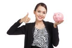 Den asiatiska affärskvinnan tummar upp med svinmyntbanken Royaltyfri Fotografi