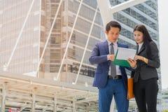 Den asiatiska affärsman- och affärskvinnan står i staden och talar om affärsframgång royaltyfri bild