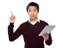 Den asiatiska affärsmanblicken på den digitala minnestavlan och fingret pekar upp Royaltyfri Foto