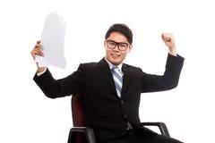 Den asiatiska affärsmannen sitter på kontorsstol som är lycklig med framgång med arkivbild
