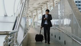 Den asiatiska affärsmannen som går släpande bagage för att gå ut med hast Royaltyfri Fotografi