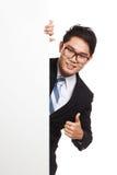 Den asiatiska affärsmannen som kikar tom banershow, tummar bakifrån u Arkivfoto
