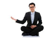 Den asiatiska affärsmannen som visar tomt utrymme, sitter på golv Arkivfoto