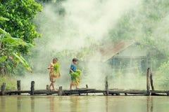 Den asiatiska barnbonden på ris korsar den wood bron för det fullvuxet i risfältfält arkivbild