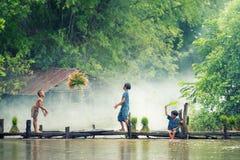 Den asiatiska barnbonden på ris korsar den wood bron för det fullvuxet i risfältfält royaltyfria foton