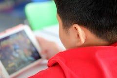 Den asiatiska barnpojken är vanebildande spela minnestavlan och mobiltelefoner Arkivfoton