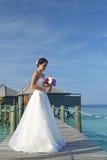Den asiatiska bruden i sjösidabröllop poserar Arkivfoto