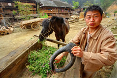 Den asiatiska byn, den lantliga kinesiska bondaktiga bonden är den hållande häst-sänkan Arkivbilder