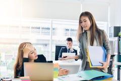 Den asiatiska chefen för affärskvinnan ger en beställning till sekreteraren i en modern kontorsaffär arkivbild