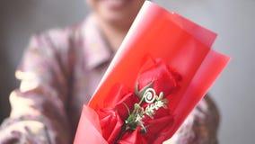 Den asiatiska damen med leende ger en bukett av en röd ros till dig långsam rörelse