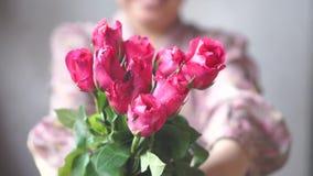 Den asiatiska damen med leende ger en bukett av rosa rosor till dig långsam rörelse för dag för valentin` s Fokus på rosor