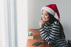 Den asiatiska det klädersanta för den tonårs- flickan hatten och leendet vänder mot att vila hennes chi royaltyfri foto