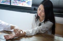 Den asiatiska doktorn kontrollerar puls för patiens` s vid fingrar arkivbilder