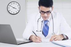 Den asiatiska doktorn skriver medicinrecept Arkivfoton