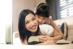 den asiatiska dottern kramar modern Arkivfoto