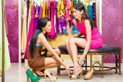 Den asiatiska försäljningsdamen shoppar in erbjudande skor Fotografering för Bildbyråer