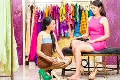 Den asiatiska försäljningsdamen shoppar in erbjudande skor Arkivfoto