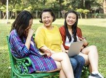 Den asiatiska familjen använder digitala apparater på parkera Arkivfoton