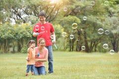 Den asiatiska familjen blåser såpbubblor tillsammans arkivbild