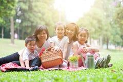 Den asiatiska familjen har picknick utomhus Royaltyfri Fotografi