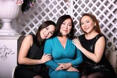 Den asiatiska familjen, mamman och dottern i aftonkappor sitter på soffan royaltyfria bilder