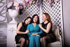 Den asiatiska familjen, mamman och dottern i aftonklänningar sitter på soffan arkivfoton