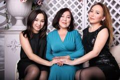Den asiatiska familjen, mamman och dottern i aftonklänningar sitter på soffan royaltyfri foto