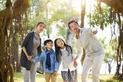 Den asiatiska familjen med två barn som har gyckel parkerar in arkivfoto