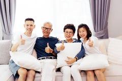 Den asiatiska familjen med vuxna barn och pensionären uppfostrar att ge upp tummar och att koppla av på en soffa hemma tillsamman arkivbild