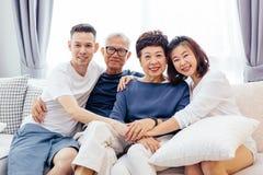 Den asiatiska familjen med vuxna barn och pensionären uppfostrar att koppla av på en soffa hemma tillsammans royaltyfria foton
