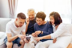 Den asiatiska familjen med vuxna barn och pensionären uppfostrar genom att använda en mobiltelefon och koppla av på en soffa hemm arkivfoto
