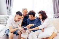Den asiatiska familjen med vuxna barn och pensionären uppfostrar genom att använda en mobiltelefon och koppla av på en soffa hemm arkivfoton