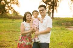Den asiatiska familjen på den utomhus- trädgården parkerar Arkivfoto