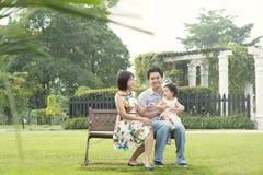 Den asiatiska familjen som har gyckel på det utomhus-, parkerar Arkivbilder