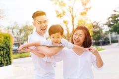Den asiatiska familjen som har roligt och bär ett barn parkerar offentligt royaltyfri fotografi
