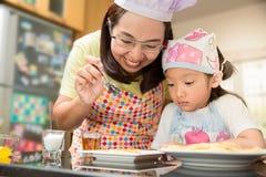 Den asiatiska familjen tycker om framställning pannkakan, asiatisk moder, och dottern tycker om framställning bagerit Fotografering för Bildbyråer
